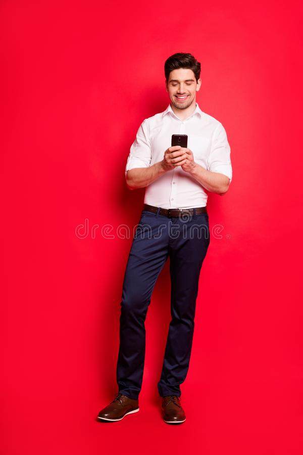 Vertical full length body size photo of handsome man watching something funny on his phone while isolated with red. Vertical full length, body size photo of royalty free stock images
