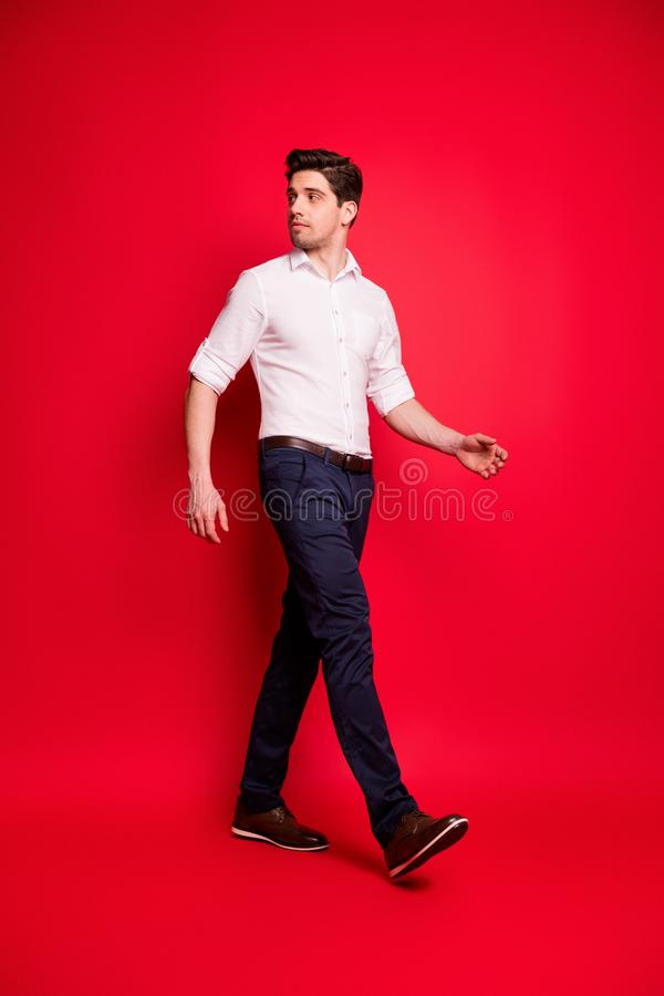 Vertical full length body size photo of turned serious confident man looking back while isolated with red background. Vertical full length, body size photo of stock images