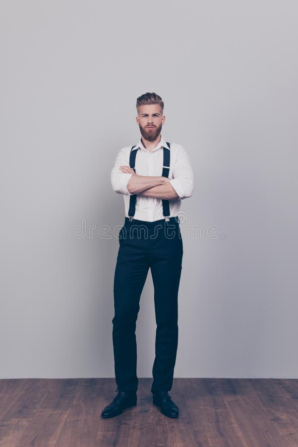 Vertical full-length full-size portrait of brutal handsome strict proud harsh authoritative bossy serious man standing with cross. Ed arms wearing formal clothes stock images