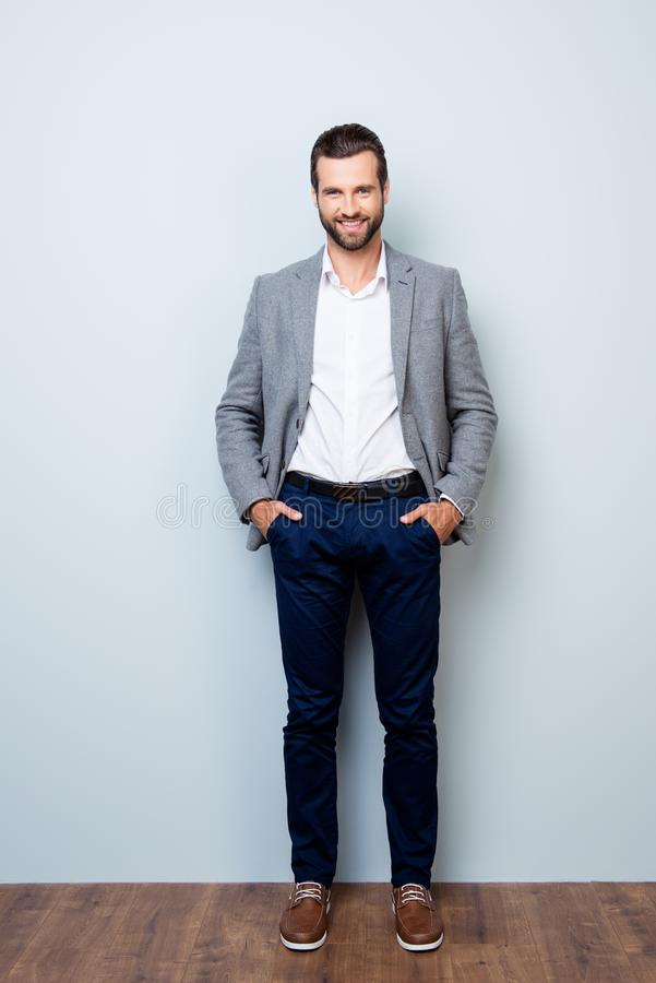Vertical full-length portrait of handsome smiling happy successful businessman holding his hands in pockets on gray background royalty free stock photography