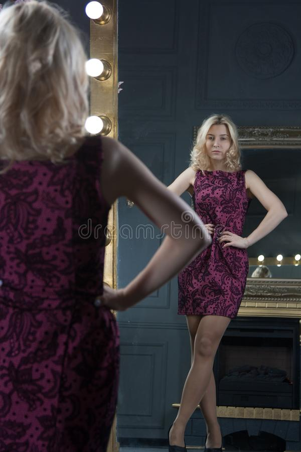 Vertical full length rearview shot of a young blonde beautiful woman fitting a new dress in front of the mirror royalty free stock photos