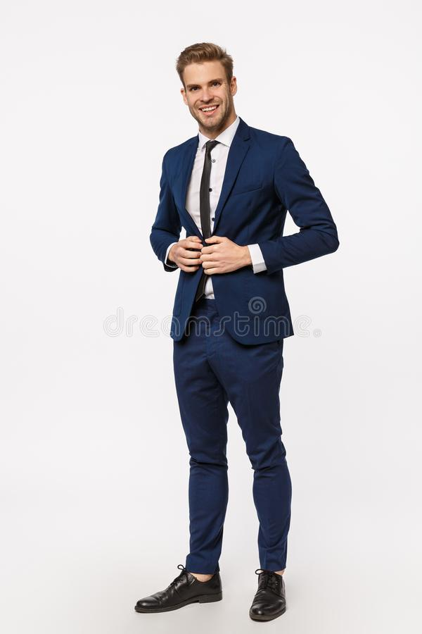 Vertical, full-length shot handsome, successful and wealthy young businessman in suit and tie, fasten buttons on jacket stock photo