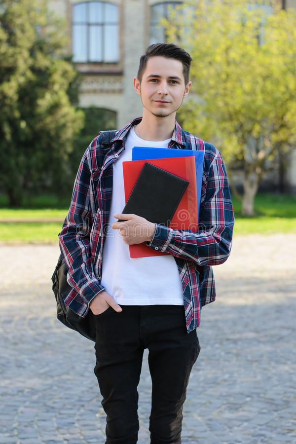 Vertical full length size body photo of intelligent guy holding pile of notebooks in hands standing near campus building royalty free stock image