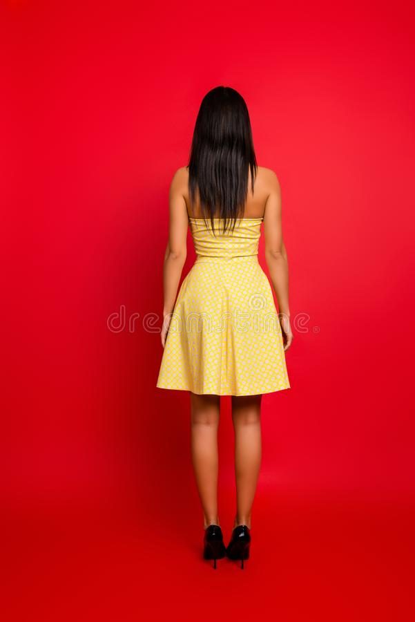 Vertical full-size rear view portrait of charming beautiful pretty woman wearing yellow dotted dress with naked stock photography