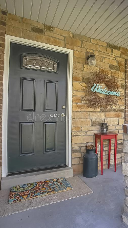 Vertical Glass paned front door and stone brick exterior wall at the facade of a home. A seating area, Welcome wreath, and ornaments can be seen on the small stock images