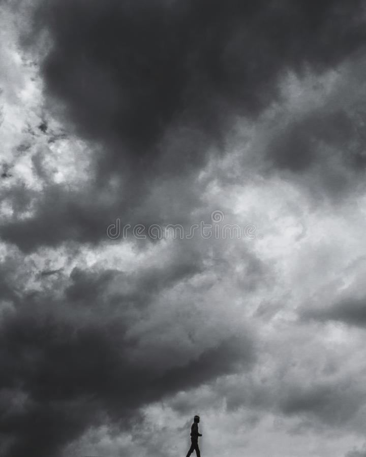 Vertical gray scale of a cloudy sky with one person at the bottom. A vertical gray scale of a cloudy sky with one person at the bottom royalty free stock photo