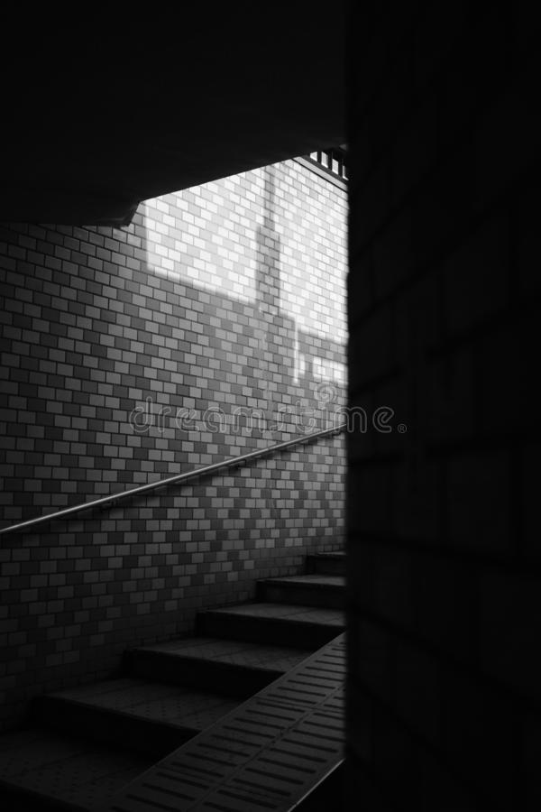 Vertical grayscale selective shot of stairs with steel handrail on a brick wall royalty free stock images