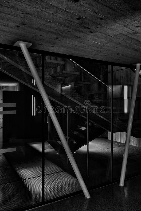 Vertical grayscale shot of the inside of a basement in a building with modern columns and staircase stock photography