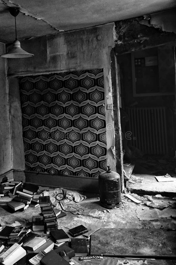Vertical grayscale shot of the interior of an old building with some forgotten books on the ground stock photography
