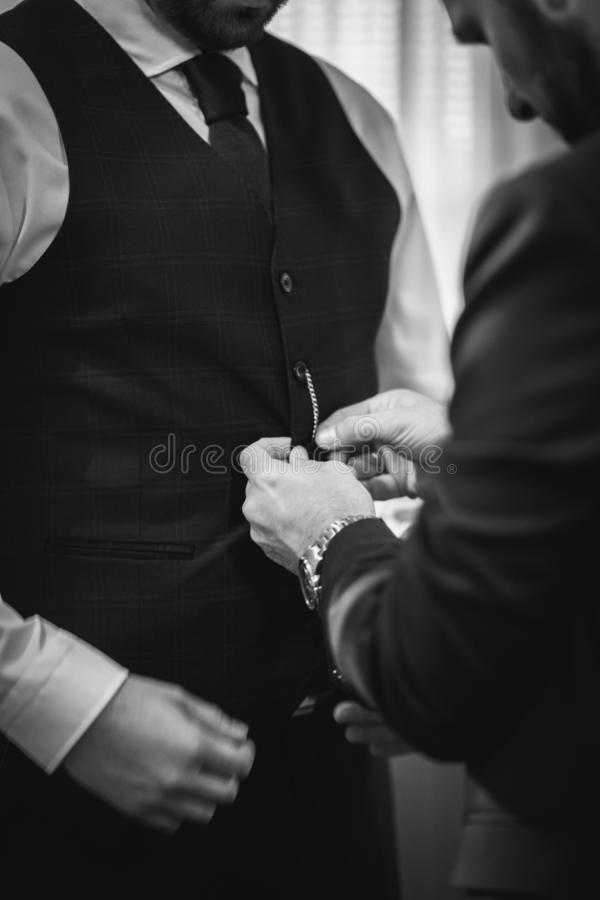 Vertical grayscale shot of a male buttoning his friend`s jacket for the wedding. A vertical grayscale shot of a male buttoning his friend`s jacket for the royalty free stock images