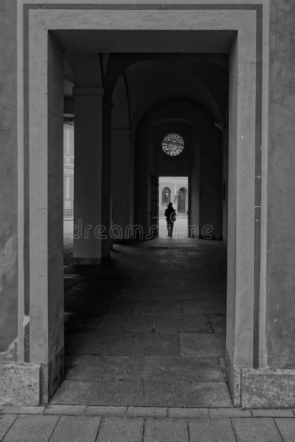 Vertical grayscale shot of a square arch and a silhouette of a person in the background. A vertical grayscale shot of a square arch and a silhouette of a person stock photography