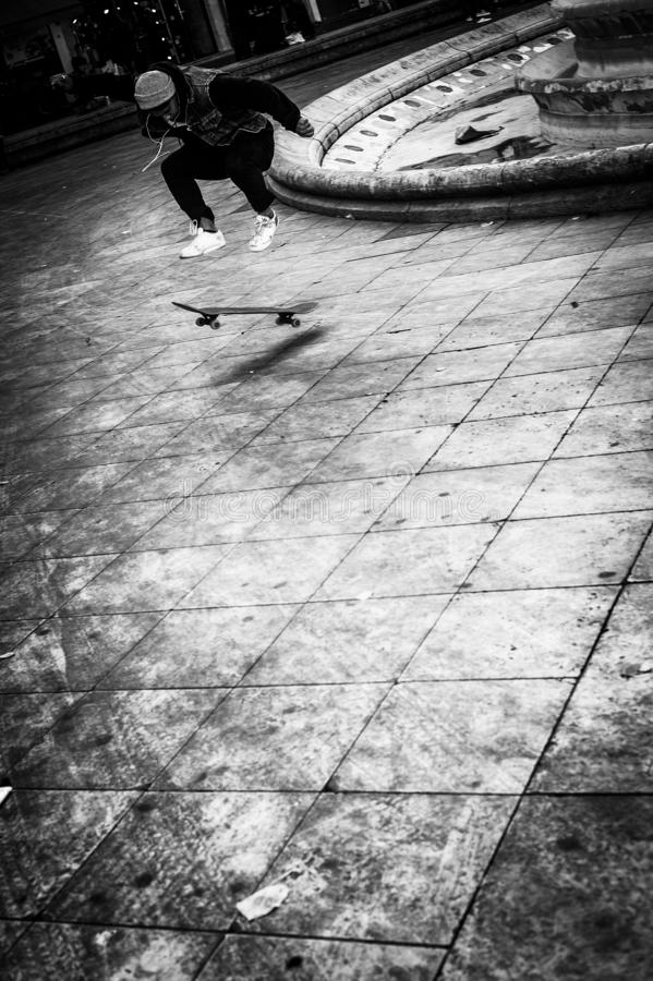 Vertical grayscale shot of a young boy in the process of a jump while skateboarding in the square stock photography