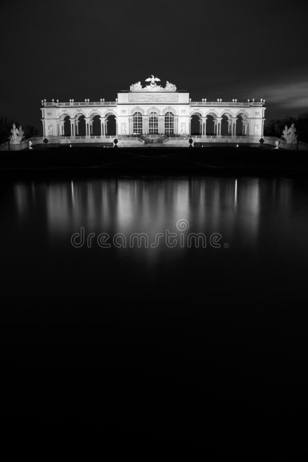 Vertical greyscale shot of a historic building reflecting on the lake in Vienna, Austria. A vertical greyscale shot of a historic building reflecting on the lake stock photo