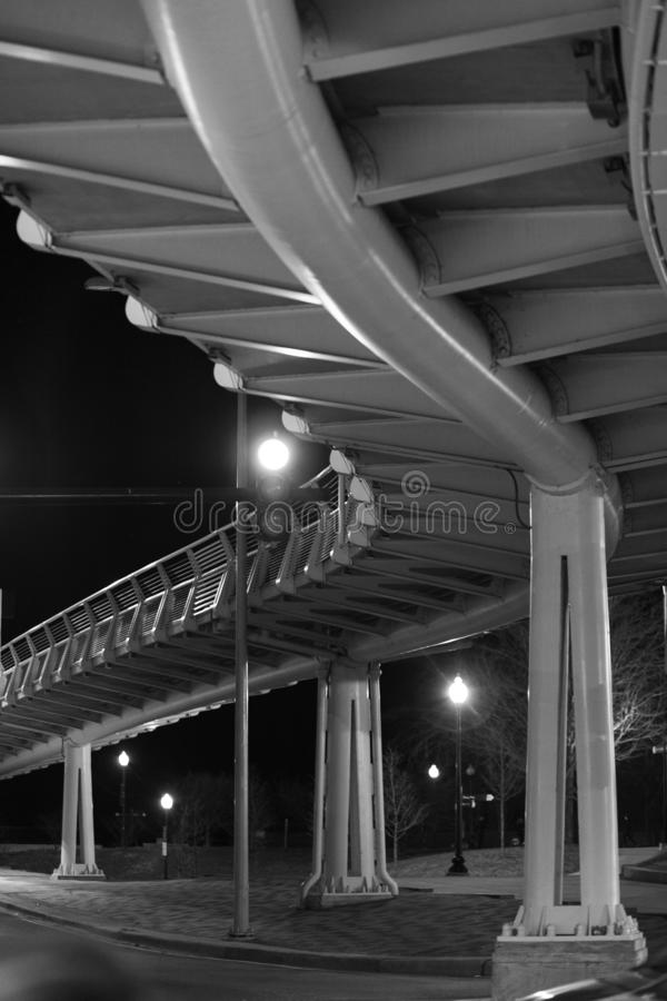 Vertical greyscale shot of a metal bridge shot at night. A vertical greyscale shot of a metal bridge shot at night stock photography