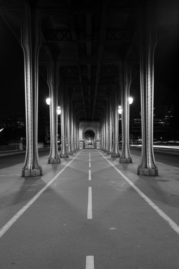 Vertical greyscale shot of a narrow road with pillars on the sides. A vertical greyscale shot of a narrow road with pillars on the sides royalty free stock photo