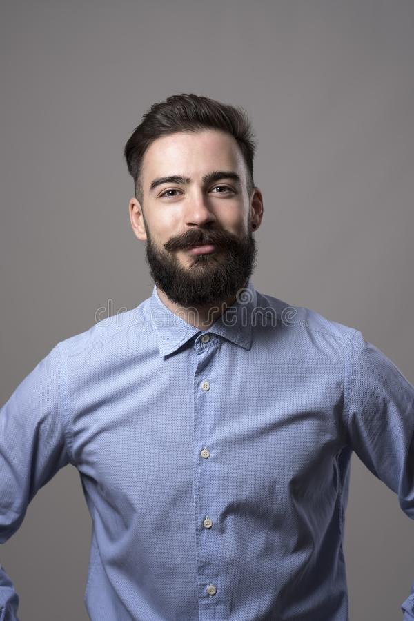 Vertical headshot of proud successful confident bearded businessman with arms on hips smiling at camera royalty free stock photo