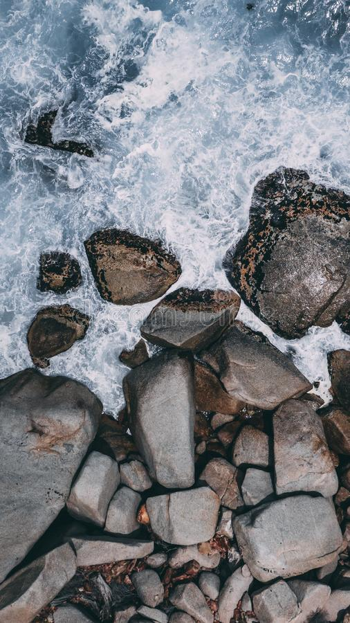 Vertical high angle shot of big stones in the stormy ocean water. A vertical high angle shot of big stones in the stormy ocean water stock images