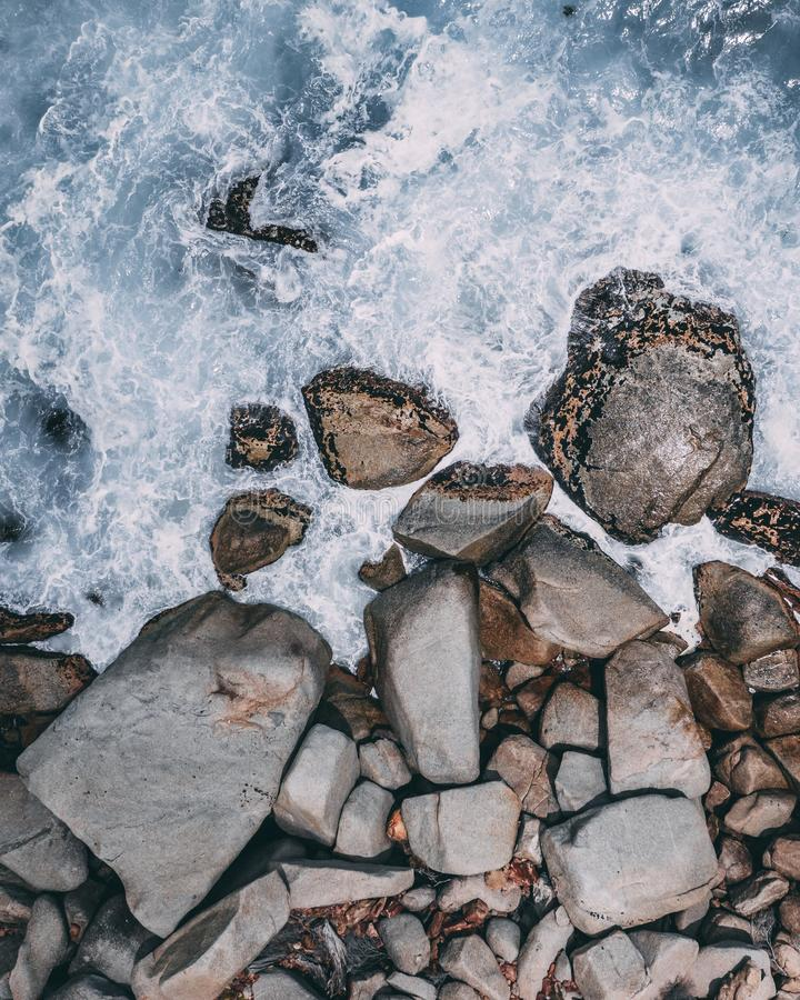 Vertical high angle shot of big stones in the stormy ocean water. A vertical high angle shot of big stones in the stormy ocean water stock image