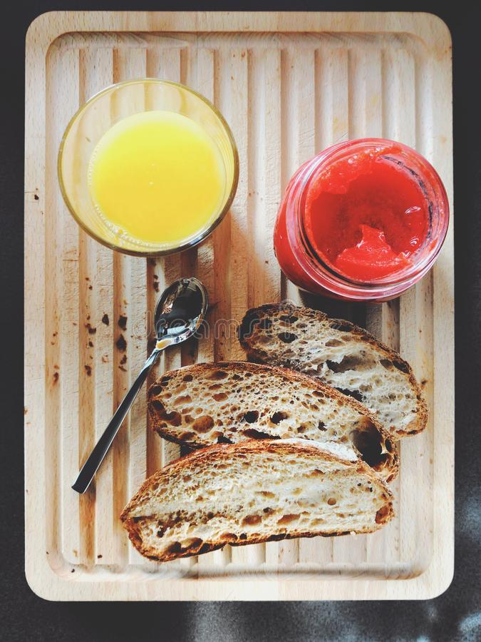 Vertical high angle shot of orange juice, jam, and slices of bread on a tray stock images
