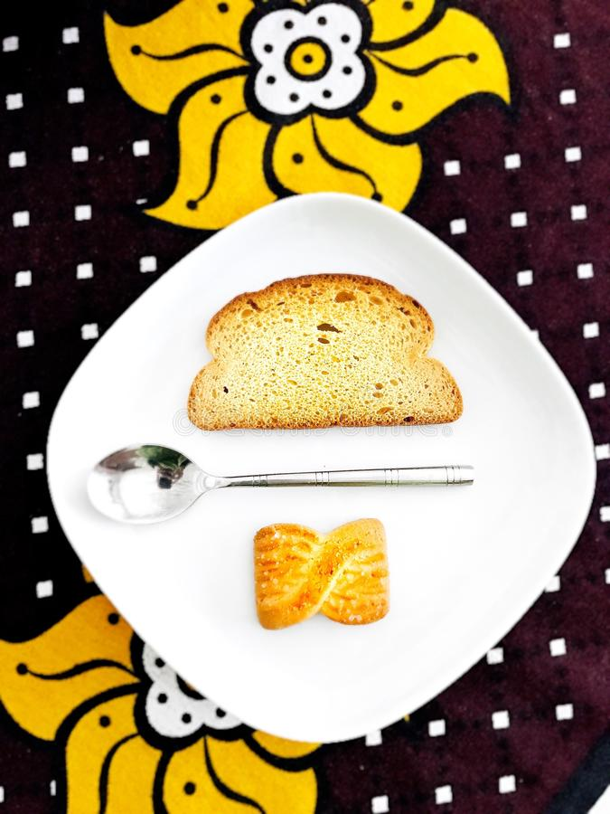 Vertical high angle shot of a silver spoon between a slice of bread and a cookie in a white plate stock image