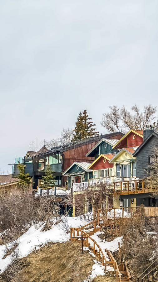 Vertical Homes with balconies on a mountain against sky filled with clouds in winter. Outdoor stairs, conifers, and leafless trees cna also be seen on the snow stock photos