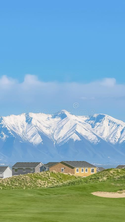 Vertical Homes and grassy field with snow covered mountain and blue sky background. A lake and valley cna also be seen on this picturesque landscape stock photography