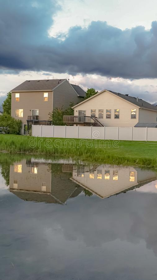 Vertical Homes and trees reflected on the shiny water of a pond amid a grassy terrain. Over the landscape is a bright sky with puffy gray clouds stock photo