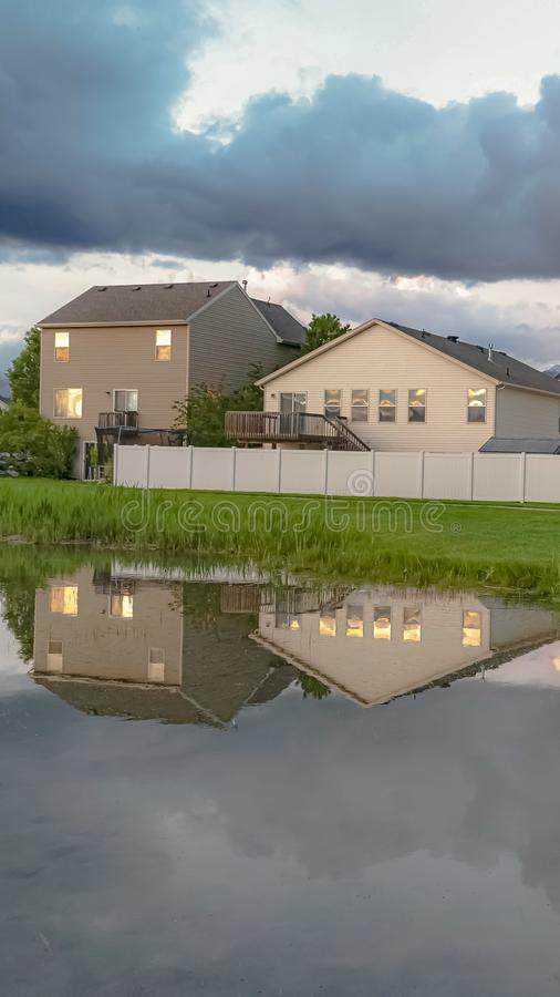 Vertical Homes and trees reflected on the shiny water of a pond amid a grassy terrain. Over the landscape is a bright sky with puffy gray clouds royalty free stock photography