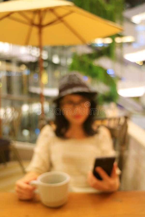 Vertical image of abstract blurred woman with a cup of coffee looking at her cell phone in the cafe stock image