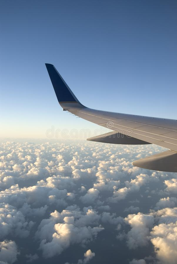 Vertical Image of Airplane Wing over Clouds Viewed form the Cabin stock photos