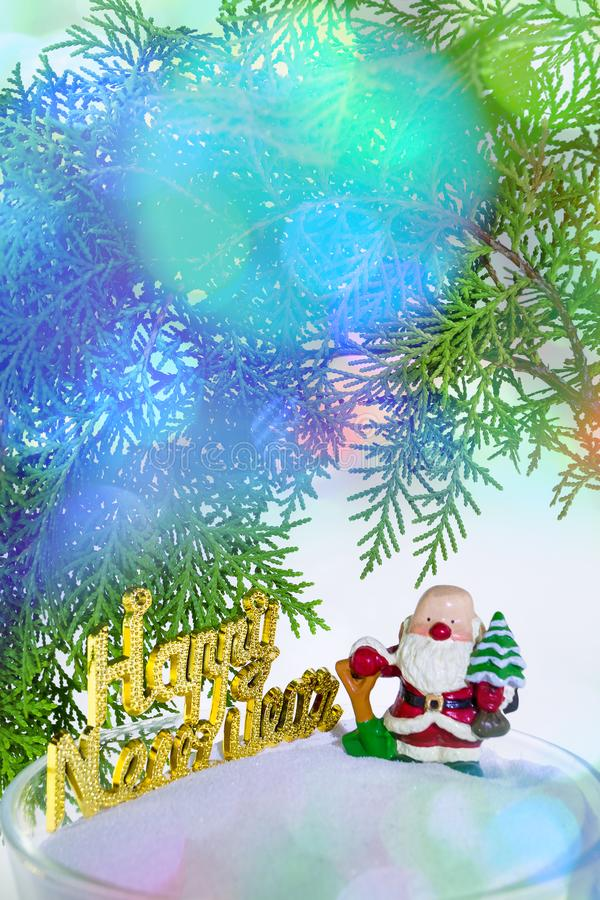 Santa doll and branch of pine tree. Vertical image with branch of pine tree and santa doll standing on snow floor with wording of Happy New year, light flare and royalty free stock images