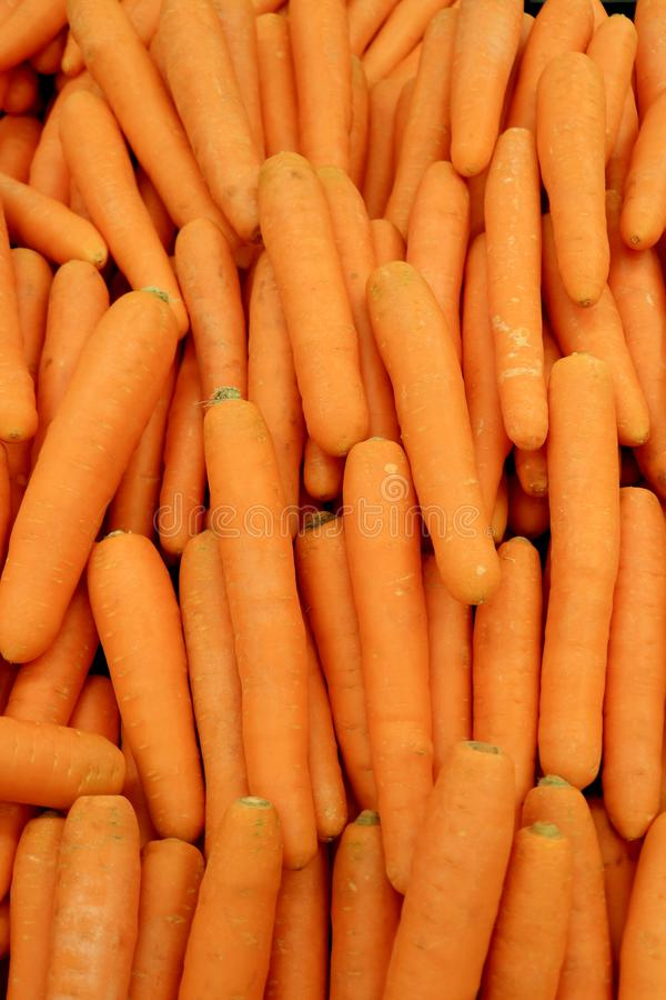 Vertical image of heap of vibrant orange color fresh carrots for background. Vertical image of heap of vibrant orange color fresh carrots for texture background stock image