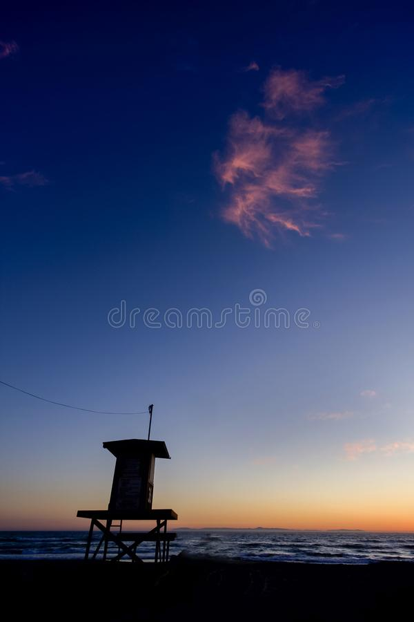 Vertical image of Lifeguard Tower at sunset with pink cloud Newport Beach Ca royalty free stock photos
