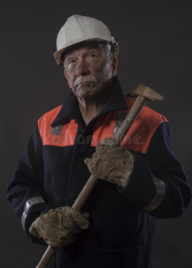 Mature miner covered in coal dust holding a pick axe. Vertical image of a mature miner covered in coal dust holding a pick axe stock photo