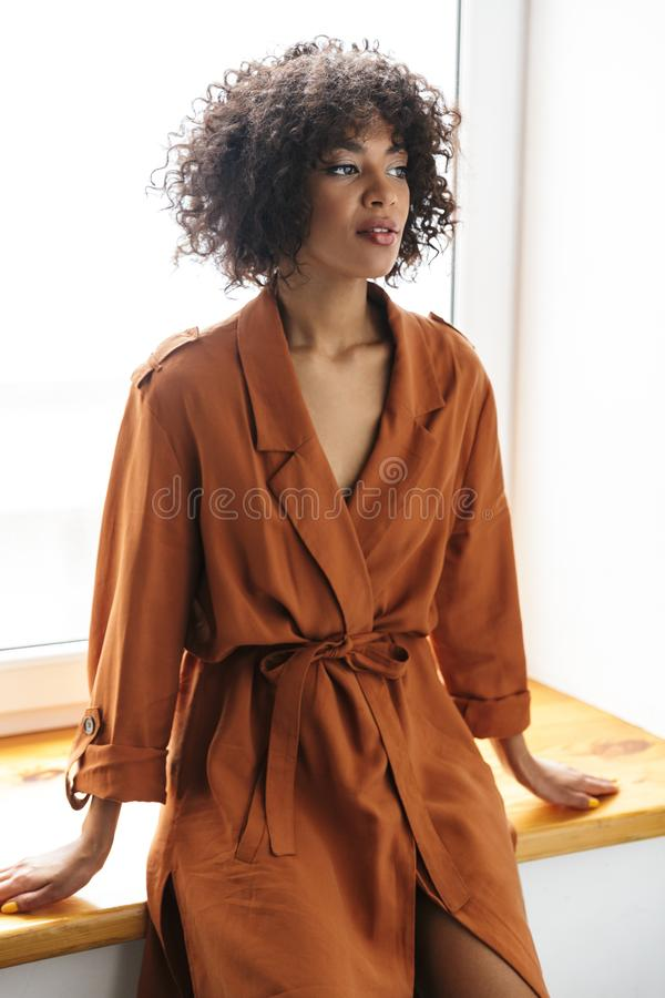 Vertical image of Mystery pretty african woman looking away stock photo