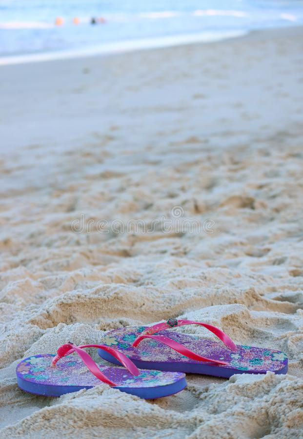 Vertical image of a pair of vibrant pink and purple flip-flops sandals on the sandy beach royalty free stock photos