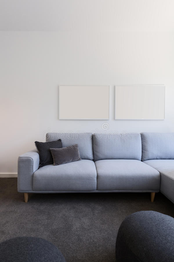 Vertical image of pastel blue sofa with blank artwork above stock photography