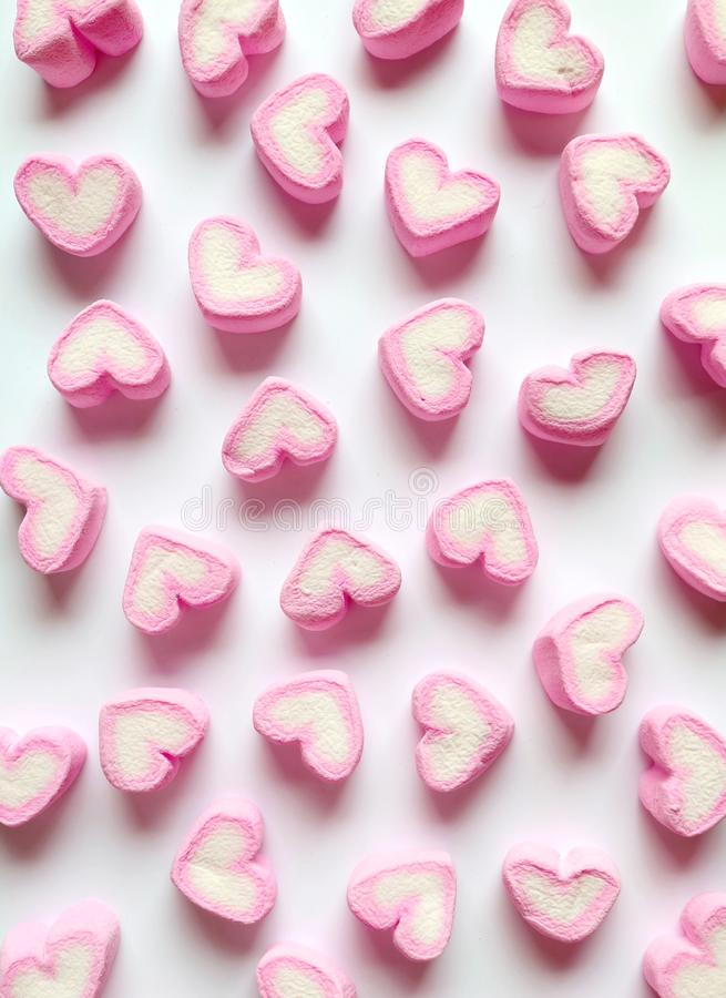 Vertical Image of Pastel Pink and White Heart Shaped Marshmallow Candies Scattered on White Background royalty free stock images