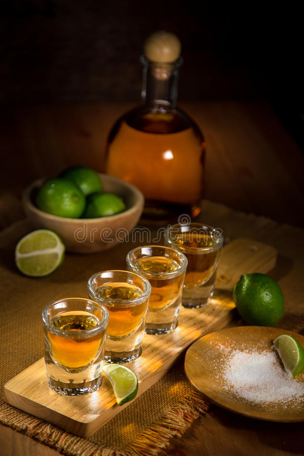 Vertical image of a serving of gold Tequila shots spread out and ready to drink at a party stock photography