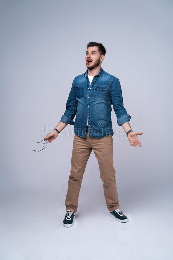 Vertical image of shocked man in shirt and jeans. Isolated on gray background. royalty free stock photography