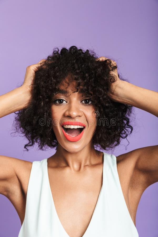 Vertical image of Surprised happy pretty african woman holding head. And looking at the camera with open mouth over violet background royalty free stock photos