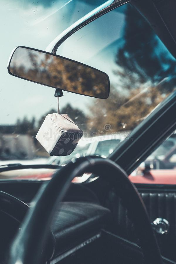 Vertical interior shot of a car with a dice hanging from a car`s mirror and a blurred background royalty free stock photos