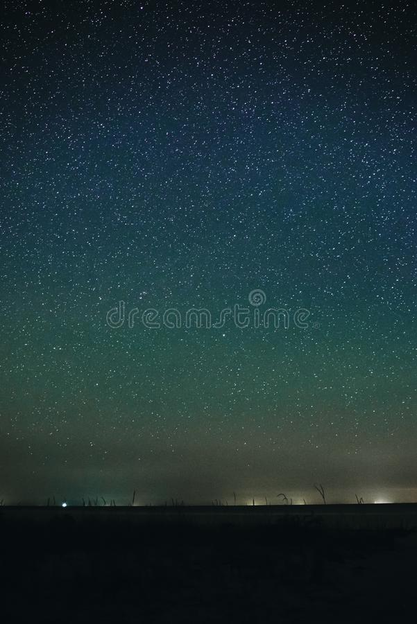 Vertical landscape of bright starry night sky with lights upon on it and sandy empty beach with grass and ocean stock image