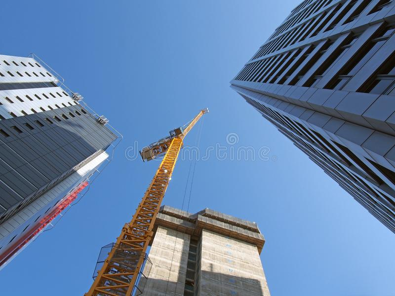 Vertical view of a tall yellow construction crane working on a new concrete building with large surrounding towers in leeds stock image