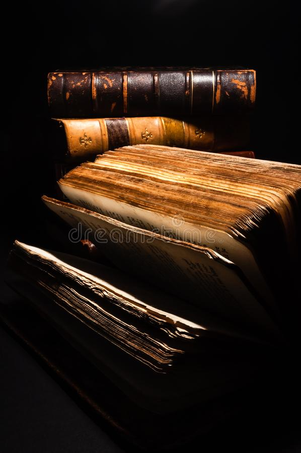 Vertical long shot of an leaned old book. With his sheets deployed ahead others old books with a hard-focus and black background royalty free stock image