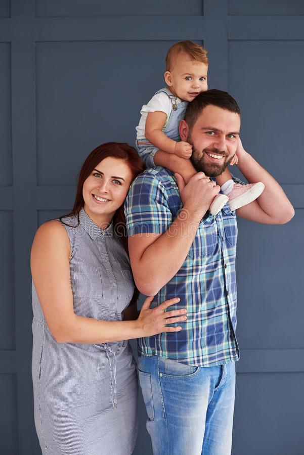 Lovely couple posing with small daughter in studio stock images