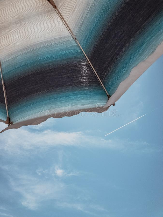 Vertical low angle shot of a blue, black and white umbrella with a blue sky in the background stock photos