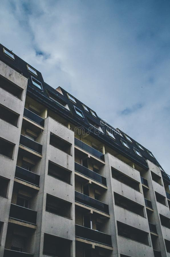 Vertical low angle shot of a blue and white building under a cloudy sky. A vertical low angle shot of a blue and white building under a cloudy sky stock images