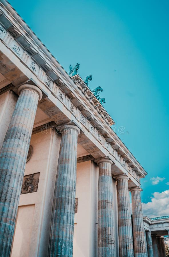 Vertical low angle shot of the Brandenburg Gate in Berlin under the bright pure sky. A vertical low angle shot of the Brandenburg Gate in Berlin under the bright royalty free stock photo