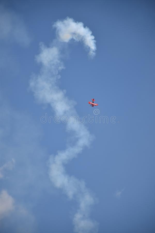 Vertical low angle shot of a red plane maneuvring in the sky and leaving a huge white trail. A vertical low angle shot of a red plane maneuvring in the sky and royalty free stock photo